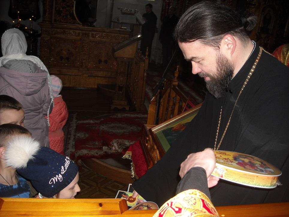 Преосвященнейший Митрофан раздает сладкие подарки детям