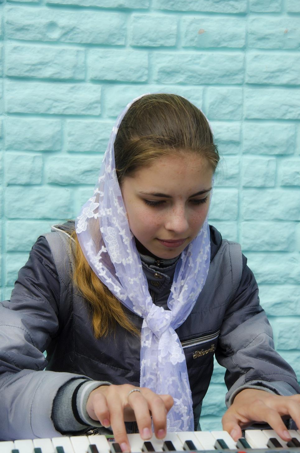Анна играет на синтезаторе.